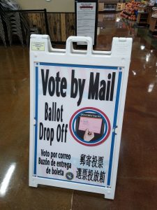 "Image of a sign which reads ""Vote by Mail"" with a ballot drop off box visible in the background."