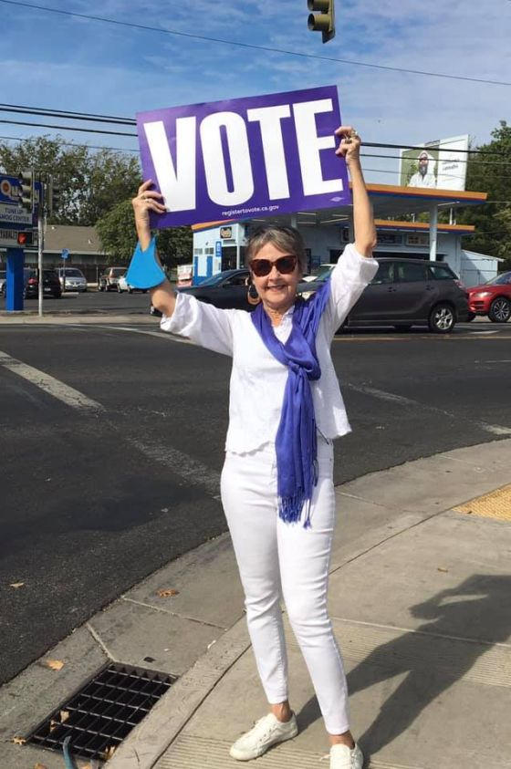 "Image of woman wearing all white with a purple scarf draped around her neck and a purple sign with the word ""vote"" in white."
