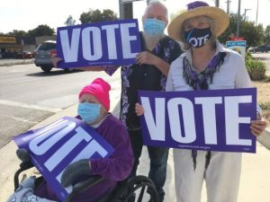 "Image of three people holding purple signs with white lettering which reads ""VOTE."""