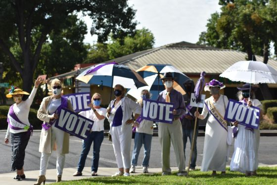 "Image of a group of people, mostly women, holding purple signs with white lettering which read ""VOTE."""