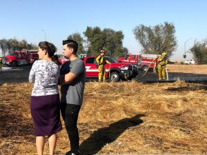 Image of woman and man watching firefighters mop of grass fire.