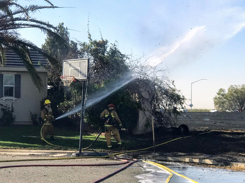 Image of firefighter hosing down vegetation growing over fence directly next to a home.