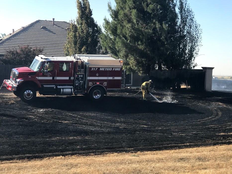 Image of firefighter hosing down burned grass. Burnt fence in background.