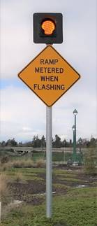 "Image of yellow caution sign which with a light mounted on top. It reads ""ramp metered when flashing."""