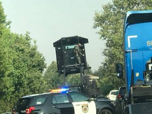 Image of SWAT officer standing on top of SacPD patrol car holding up a shield.