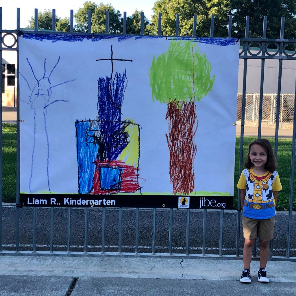 Image of small boy standing next to banner inspired by his drawing.