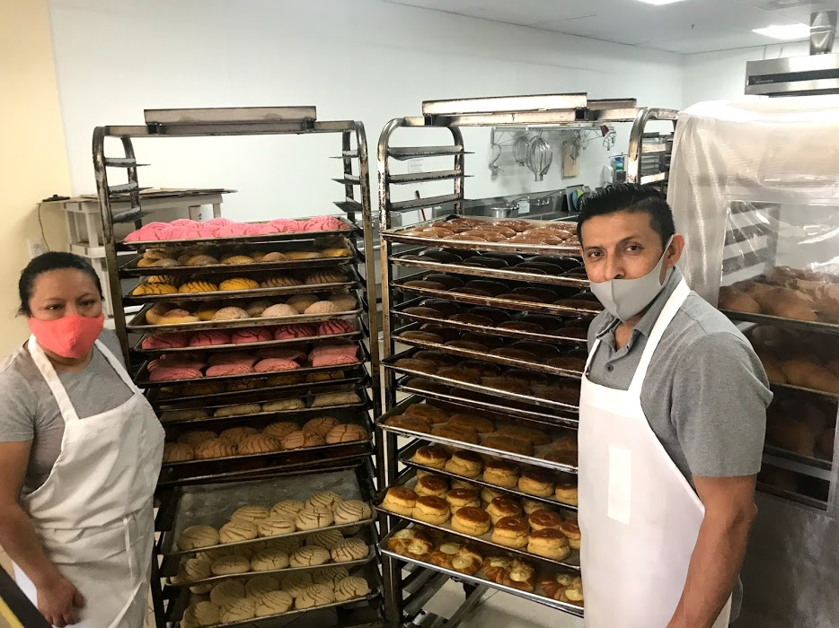Image of woman and man standing next to stacked trays of Mexican pastries.