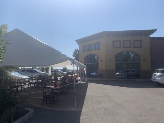 Image of parking lot with restaurant in background and tables and chairs outdoors covered by a canopy.