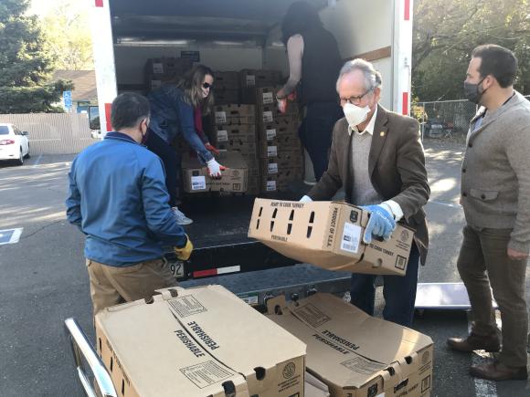 Image of city councilmember Jeff Harris unloading frozen turkeys from a truck.
