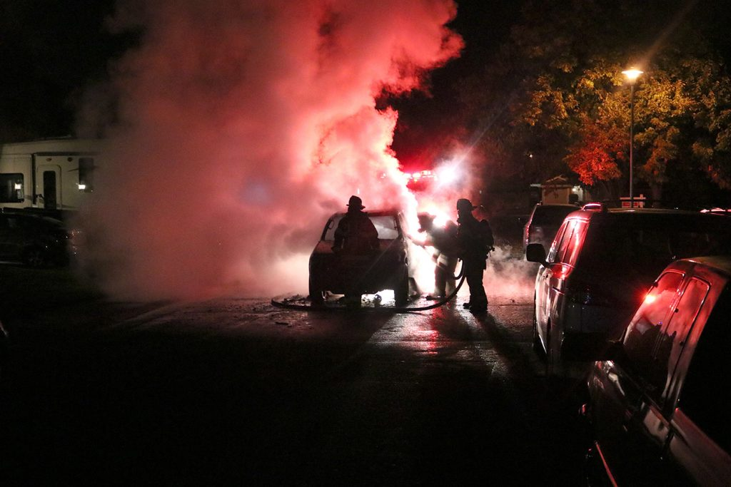 Image of vehicle engulfed in flames. Silhouettes of firefighters visible.