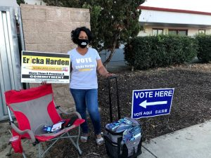Image of Ericka harden holding campaign signs on Election Day.