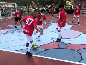 Image of three boys vying for soccer ball on hard futsal court.