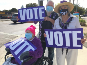 Image of three people holding purple signs that read VOTE. One is in a wheelchair.