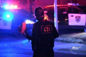 Image of back of police officer wearing CSI vest.