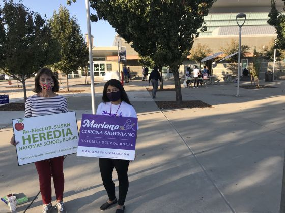 Image of two women holding campaign signs by library.
