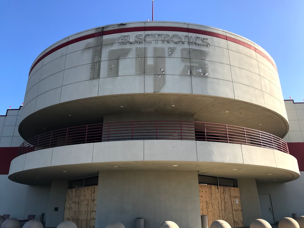 Image of round cement building with shadow of previous signage reading Fry's Electronics.
