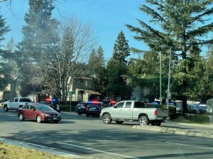 Image of several police vehicles blocking entrance to an apartment complex.
