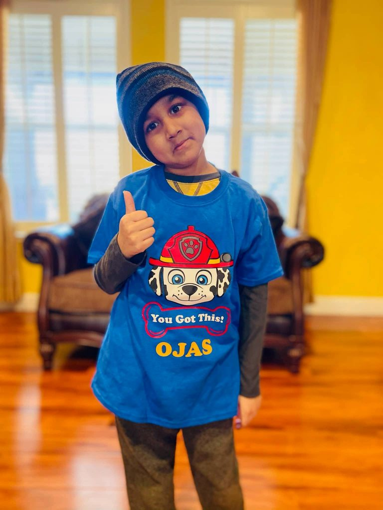 "Image of boy wearing beanie on his head giving a thumbs up. He's wearing a t-shirt which reads ""You Got This! Ojas"""